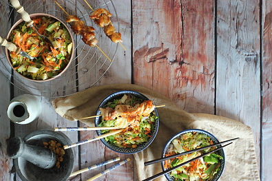 Bowls of healthy Asian food topped with chopsticks.