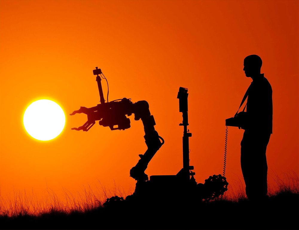 Man controlling robot with sunset backdrop