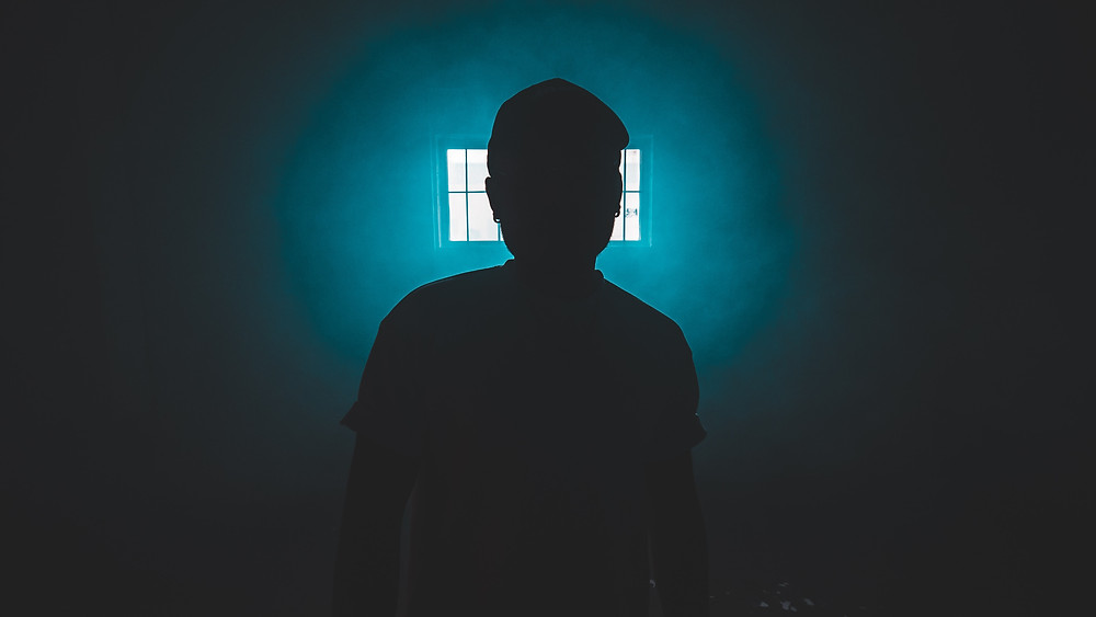A Man is in a cell type room, He is in sillouette in front of a barred window.  The Light from the Window is Flaring into a Blue Turquoise Colour and it give the man a halo of Blue Light.