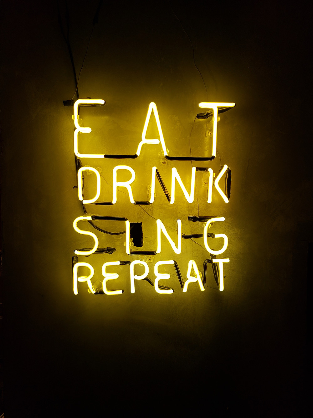 "A neon sign that reads ""Eat, Drink, Sing, Repeat""."