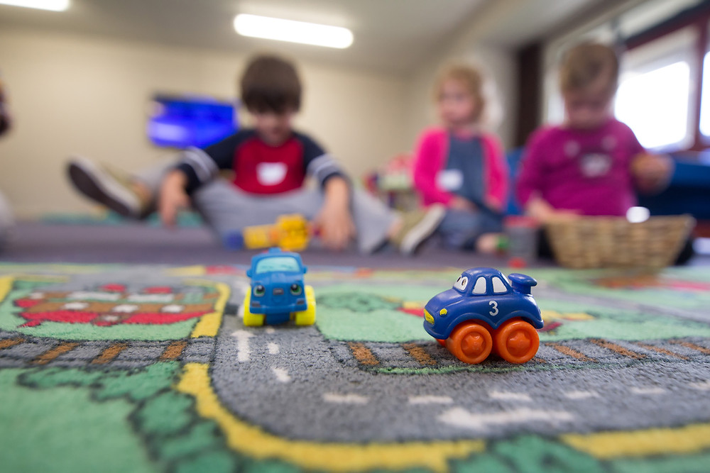 Children playing with cars on a city carpet at a preschool