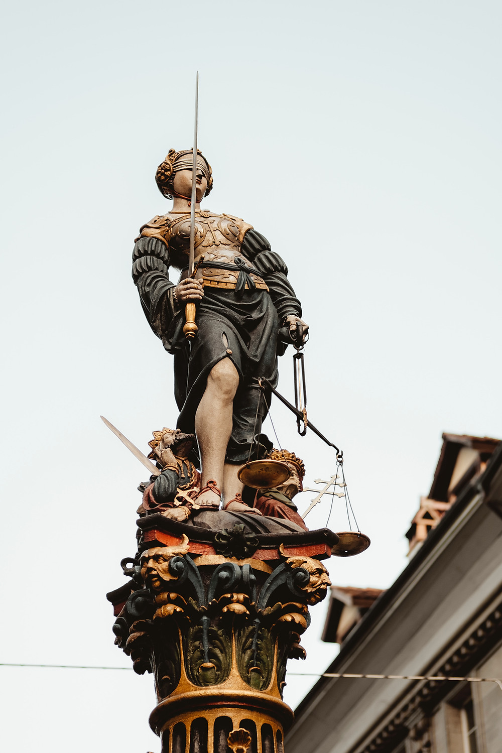 justice blindfolded holding a sword and scale