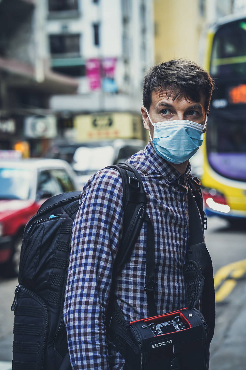 Man in a busy city wearing a medical mask.