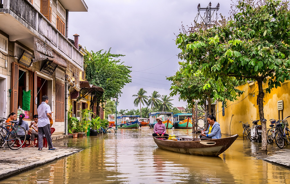 a dugout boat moving through a flooded street in a tropical town.
