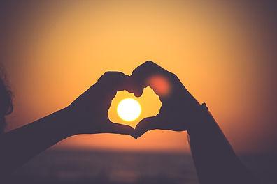 Hands shaping a heart, sun coming through