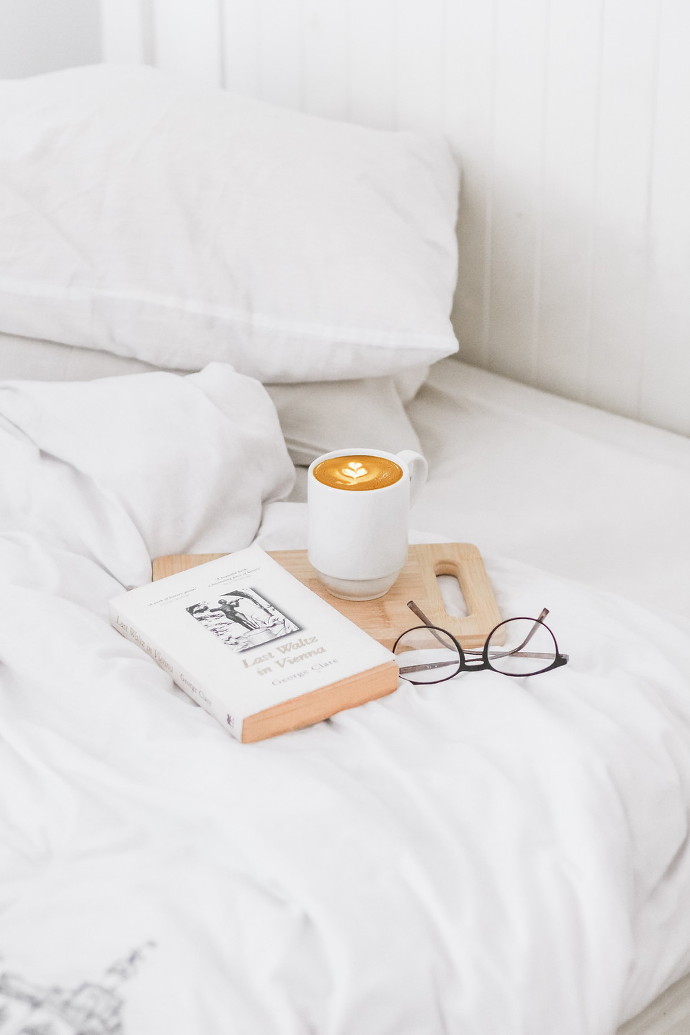A coffee, glasses and a book lie on a bed which is made up with clean, white bedding