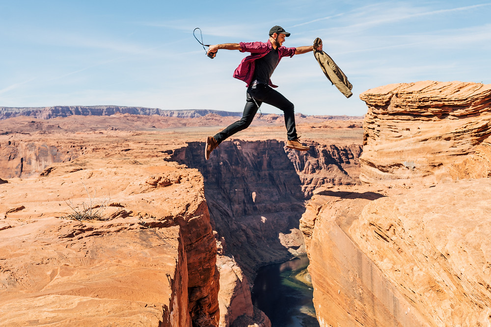 Photo of man jumping across a crevasse.