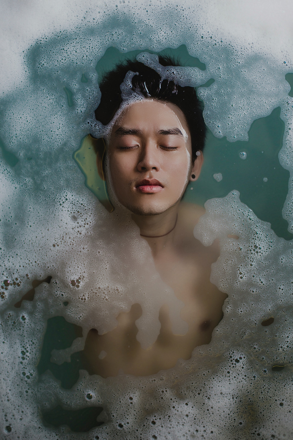 A man practices self-care while floating in sudsy water.