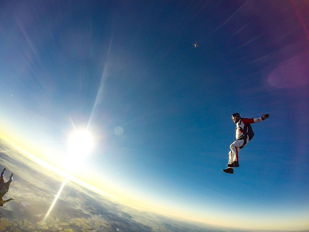 skydiver falling through sky with gear on