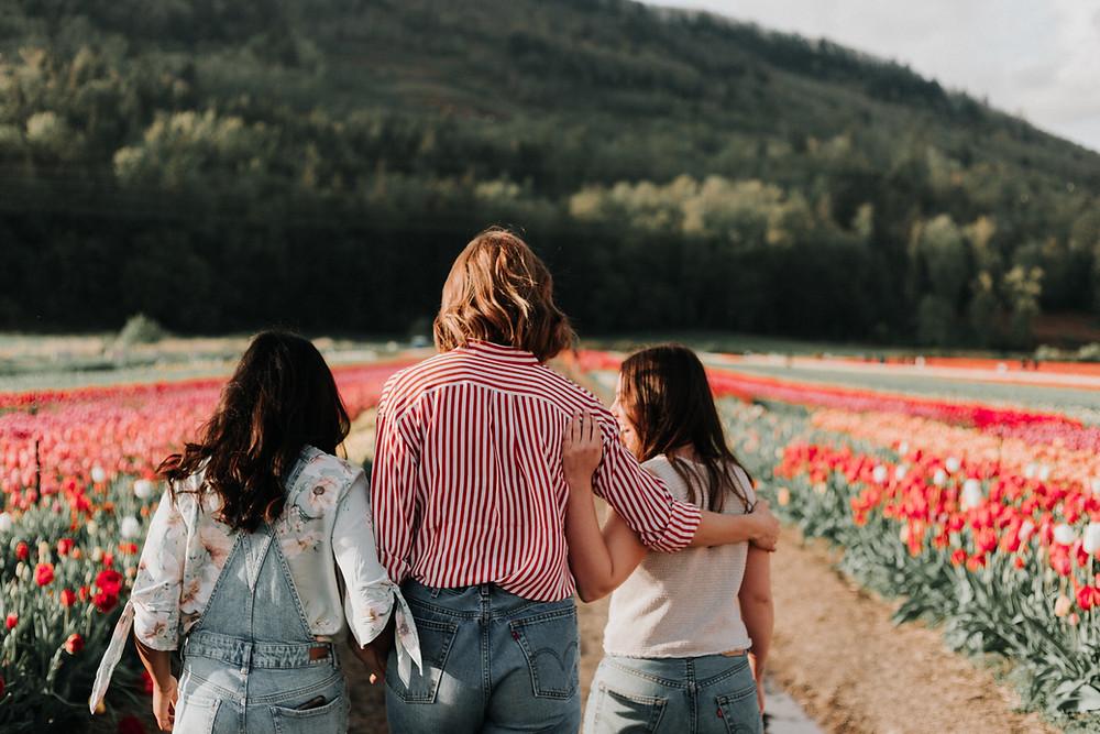 Three women walk in a field of tulips