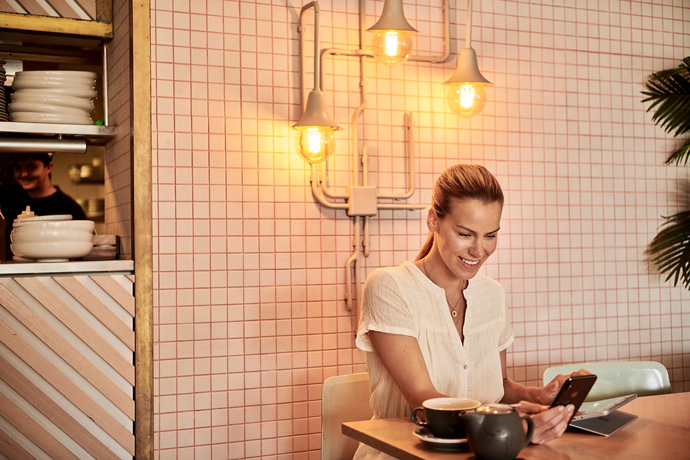 woman planning week on phone in cafe