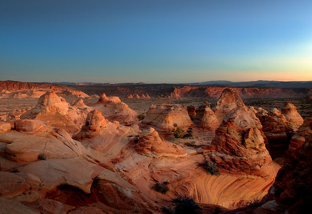 Expansive sunset view of desert rock formations in Monument Valley, Utah