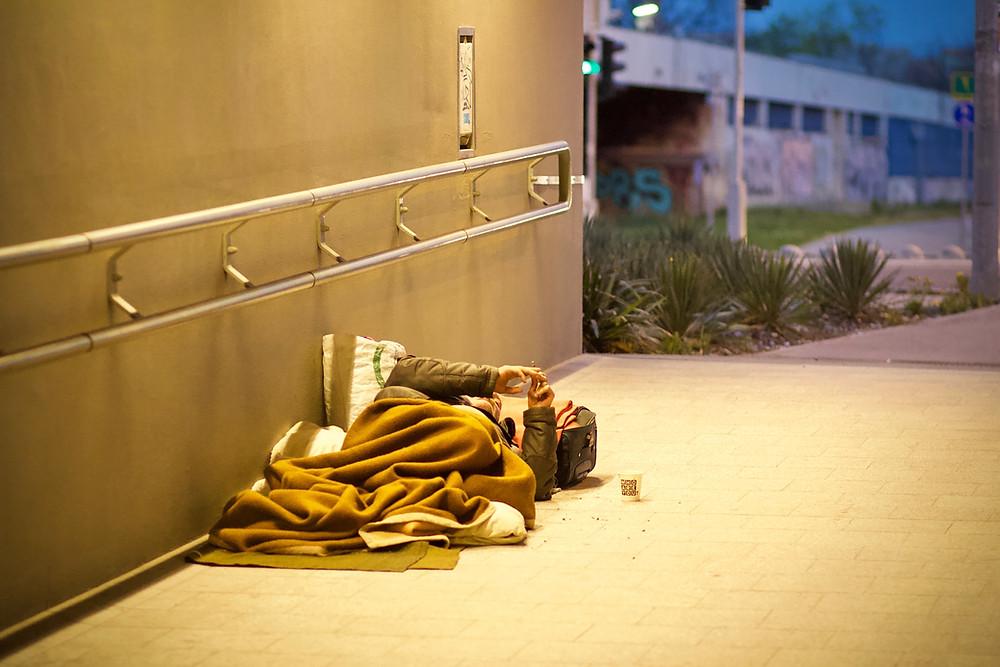 Homeless person sleeping on a sidewalk