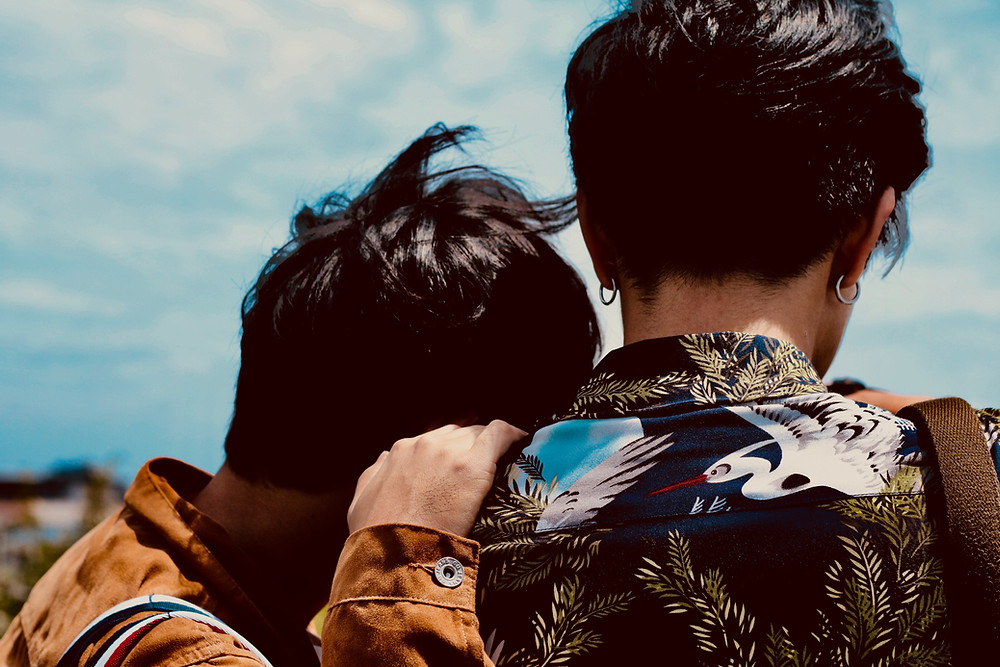 Asian male couple, back view, near water