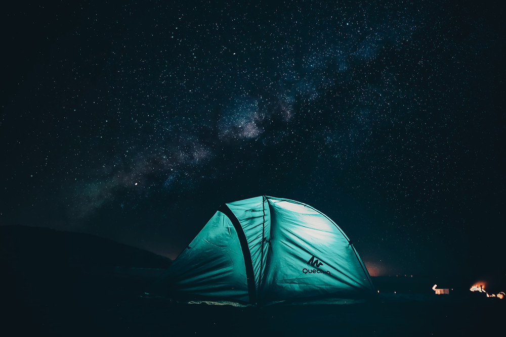 Illuminated blue tent under dark night sky with visible milky way in Glacier National Park