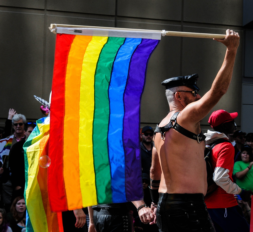 Mature Gay Leather Daddy with LGBTQ rainbow flag