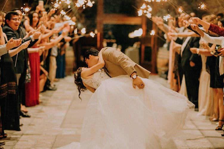 Les mariés, habillés pour l'occasion s'embrassent en dansant et sont applaudis par les invités de l'événements qui ont tous le sourire et des batons lumineux dans les mains