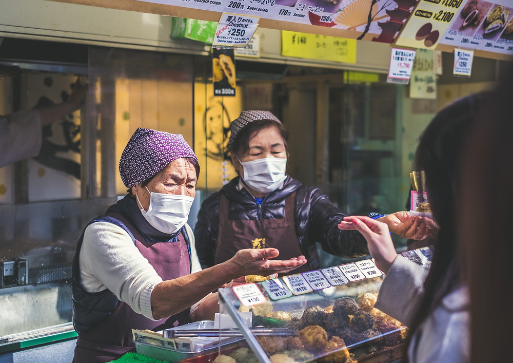 Women in China wear face masks while working at a cafe