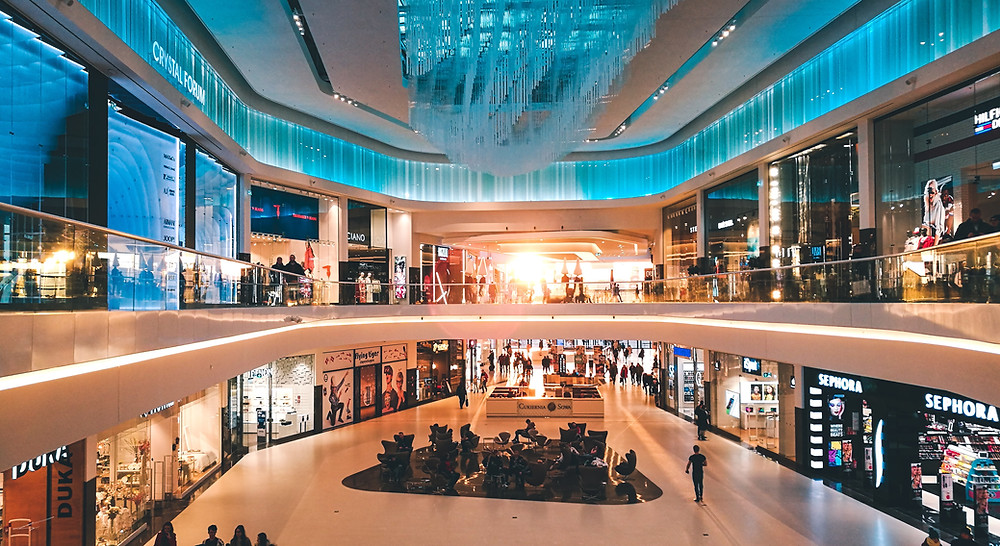 An Image of an Shopping Mall, overlooking a balcony to the ground floor below and the same floor ahead. The Mall is lit with a sky blue light and it has a warm feeling as the floors are a soft beige colour