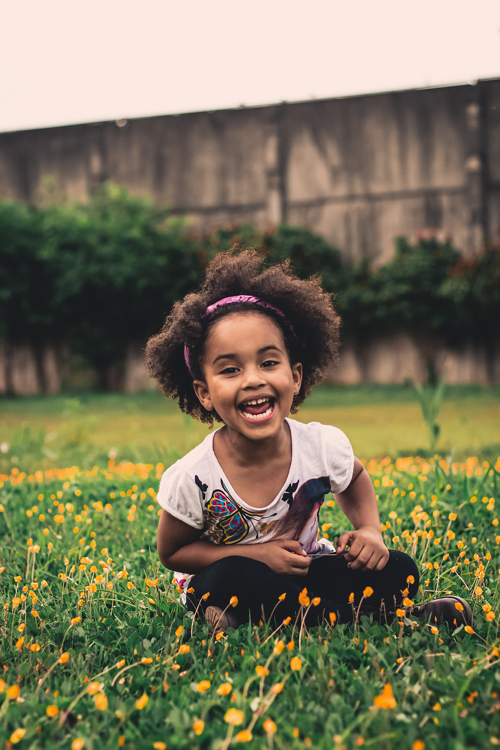 Young African American girl sitting happily in a field of small yellow flowers