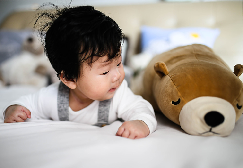 Asian baby lying on stomach looking at a brown stuffed animal.