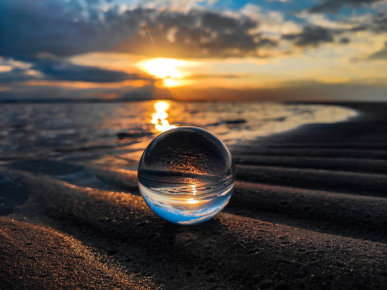 Reflection ball in front of ocean waters with the sun setting in the distance