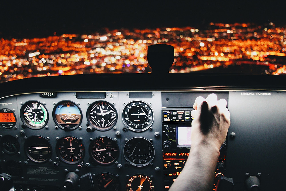 The cockpit of a plane as it overflies a city at night