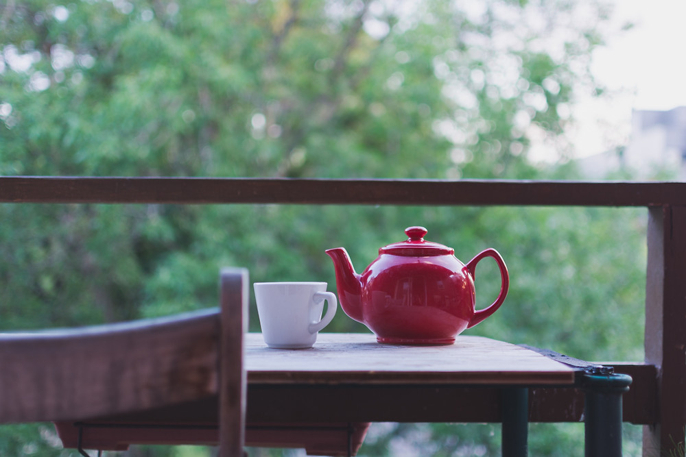 Table by a window with tea pot and mug