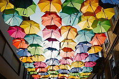 dozens of umbrellas suspended in a layer overhead with the sun behind them
