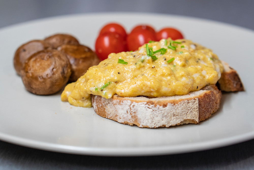Scrambled egg on toast with vegetable sides