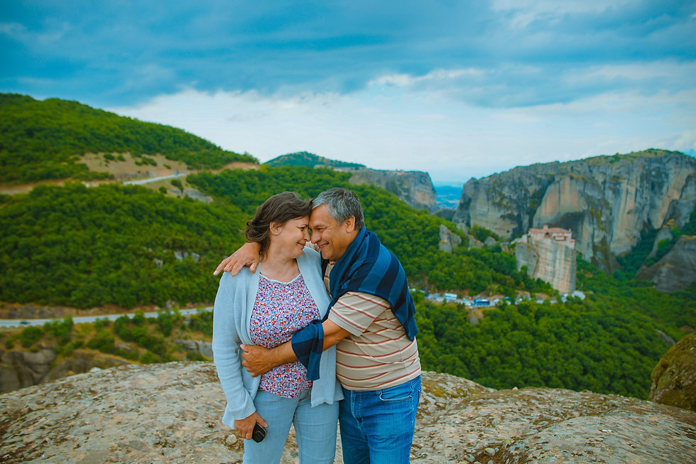 A middle aged LatinX couple smiling and  embracing with mountains in background.