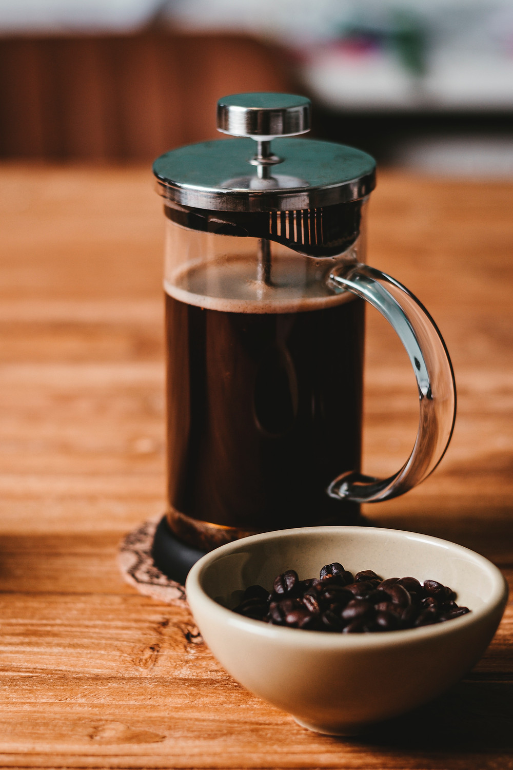 French press with cacao beans in a nearby bowl