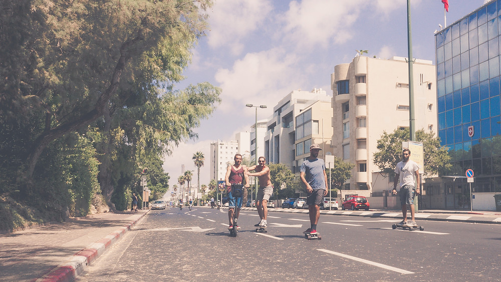 Young adults skateboarding on an empty street