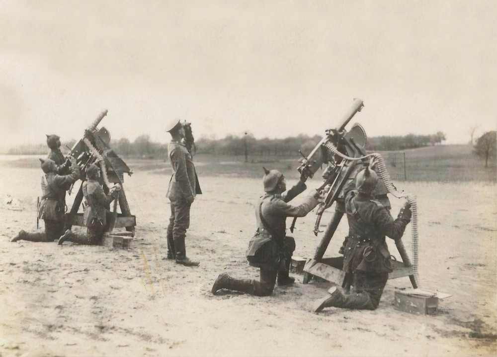 Sepia toned photo of soldiers aiming mounted guns, and a commander with binoculars