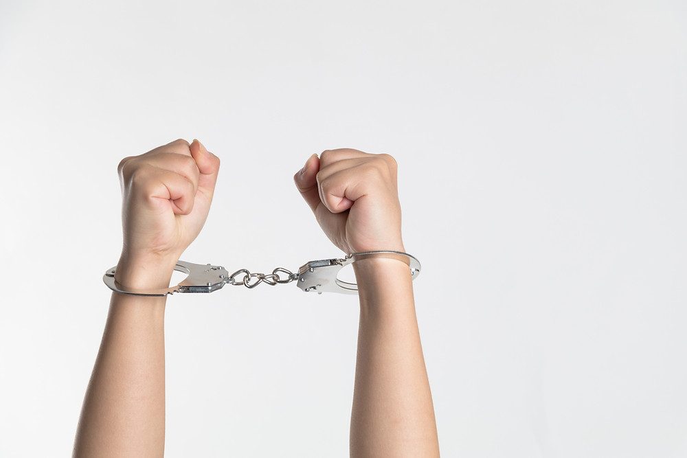 Two arms raised with fists clenched wearing metal handcuff