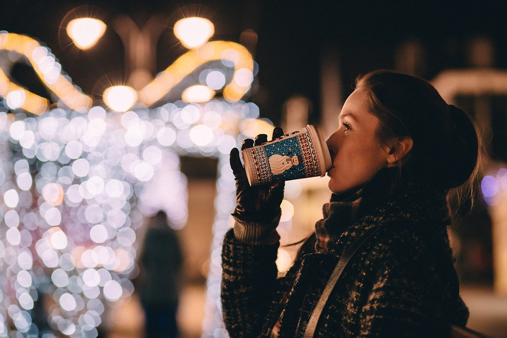 a woman drinks a cup of coffee while looking at Christmas lights