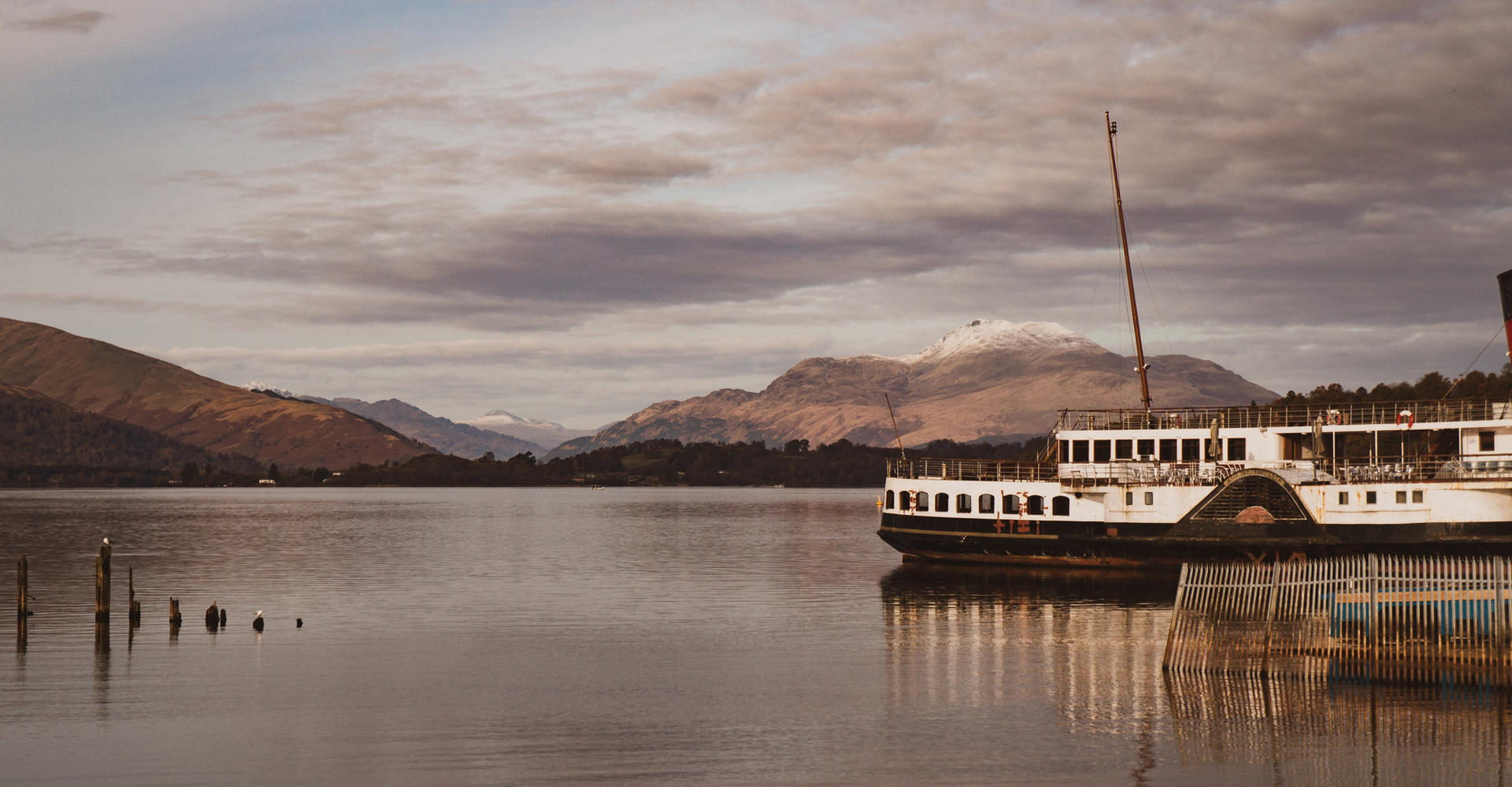 cruise boat on calm loch lomond scotland with mountains arrochar alps
