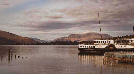 cruise boat on calm loch lomond scotland with mountains arrochar alps