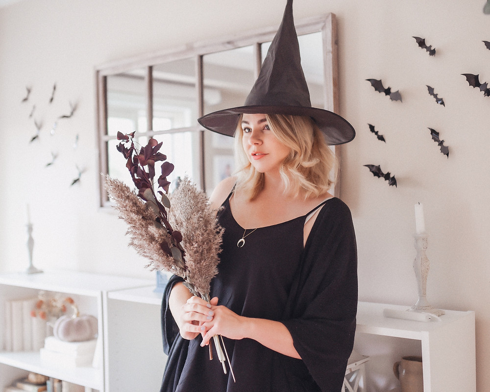 cute woman wearing a witch costume for halloween