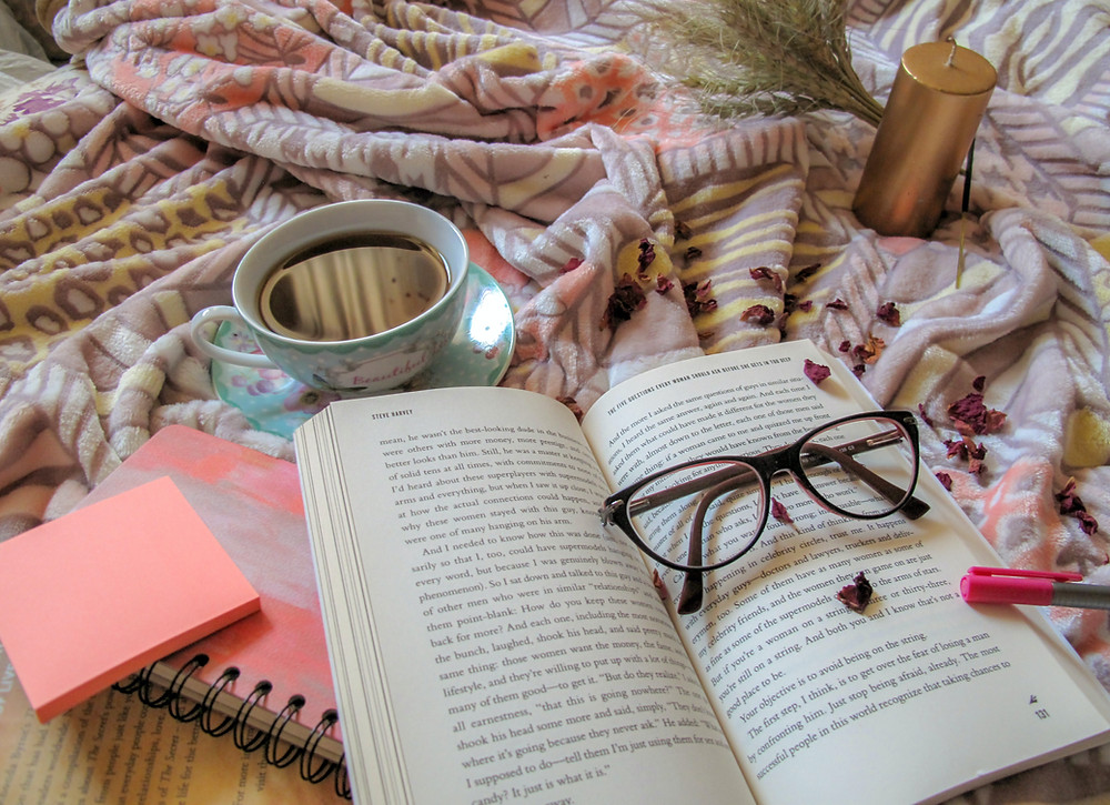 picture of cup of tea, book, and glasses on a cozy bed. You don't have to network constantly, especially now. Be kind to yourself.