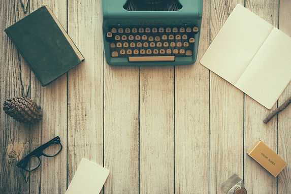 An old-fashioned green book, a retro green typewriter, and an open notebook on a wooden-slatted table.