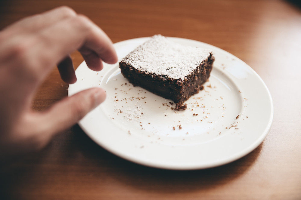 Person reaching for a brownie on a white plate