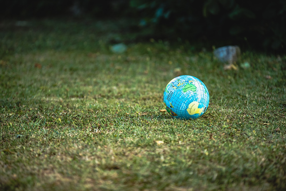 A small ball lies on a large patch of grass. The ball is a small globe, with geographical mapping on the world on its surface.
