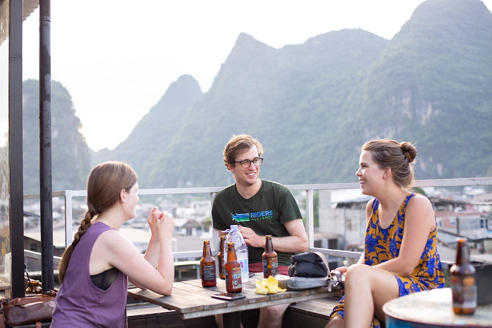 grupos com tres amigos conversando ao ar livre