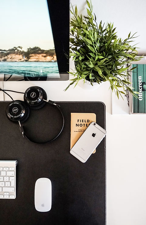 A clean and organized desk with an iphone, notepad, music headphone, and Apple computer. A presentation of a booking agent's desk. ANG Production focuses on its artists.