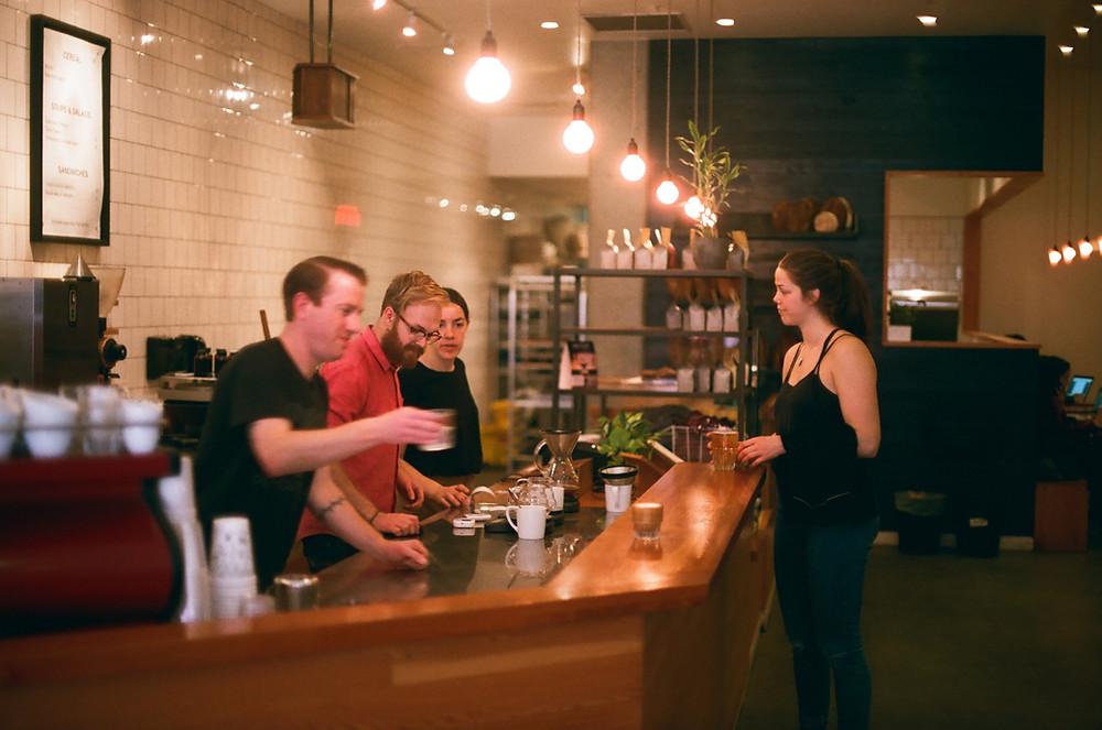 a girl in black top ordering coffee in coffee in coffee shop