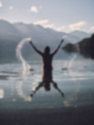 Woman standing in a mountain lake splashing water in the airImage by Nicolas Moscarda