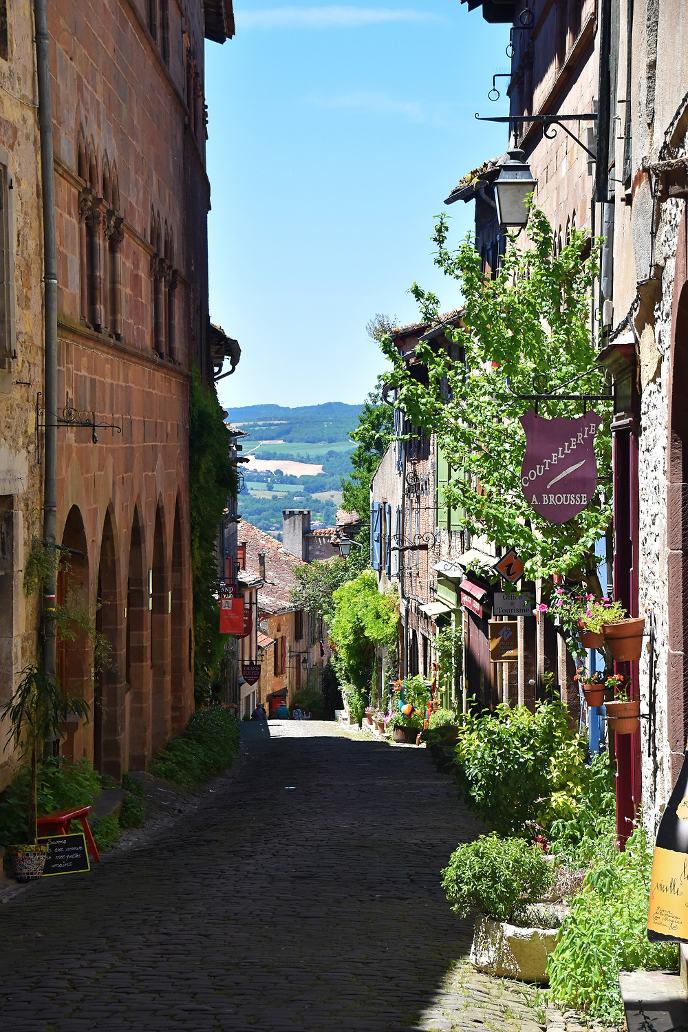 A winding medieval street in France with a view to the countryside