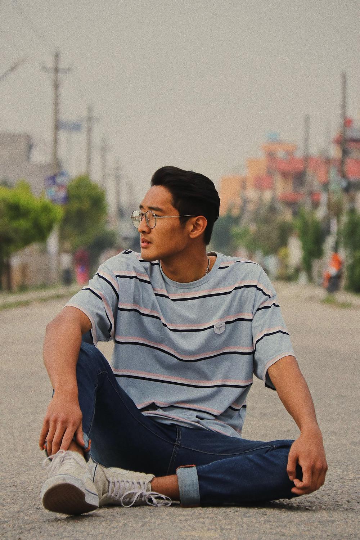 asian boy sitting on the street