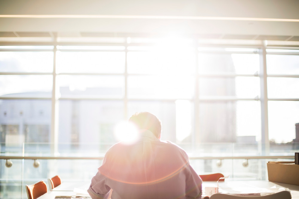 Man at desk with sun beaming in